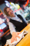 Pretty barmaid wiping down bar Stock Photo