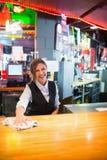 Pretty barmaid wiping down bar. In a bar Stock Photo