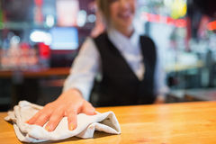 Pretty barmaid wiping down bar. In a bar Stock Photography
