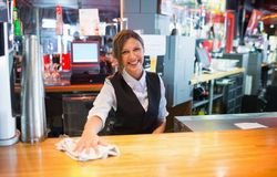 Pretty barmaid wiping down bar. In a bar Stock Images