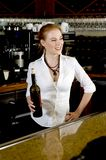 Pretty bartender. Beautiful red-haired bartender smiles at some customers, holding a bottle of red wine she just opened Stock Photography