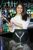 Pretty bartender mixing a cocktail drink in cocktail shaker. At bar stock image