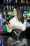 Pretty bartender mixing a cocktail drink in cocktail shaker. At bar royalty free stock image