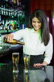 Pretty bartender pouring beer into glasses Royalty Free Stock Photos