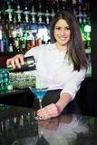 Pretty bartender pouring a blue martini drink in the glass Stock Images