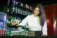 Pretty bartender pouring tequila into glasses Royalty Free Stock Photo