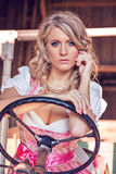 Pretty Bavarian woman with Dirndl dress driving tractor Stock Photo