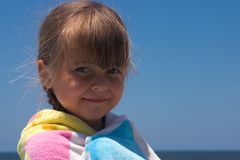 Pretty beach girl. A cute little girl wrapped in a towel at the beach royalty free stock photos