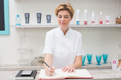 Pretty beautician writing in appointment book Royalty Free Stock Image