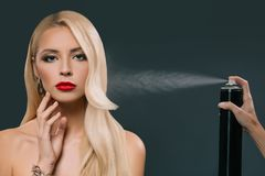 pretty beautiful blonde hair girl with hand using spray Royalty Free Stock Photos
