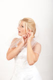 Pretty beautiful bride putting on an earring Stock Images