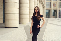 Pretty beautiful business woman in elegant black dress. Young elegant girl posing at city street. Pretty beautiful business woman in elegant black dress against Royalty Free Stock Images