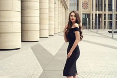 Pretty beautiful business woman in elegant black dress. Young elegant girl posing at city street. Pretty beautiful business woman in elegant black dress against Royalty Free Stock Photos