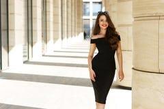 Pretty beautiful business woman in elegant black dress. Young elegant girl posing at city street. Pretty beautiful business woman in elegant black dress against Royalty Free Stock Image