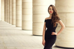 Pretty beautiful business woman in elegant black dress. Young elegant girl posing at city street. Pretty beautiful business woman in elegant black dress against Royalty Free Stock Photography