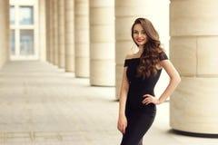 Pretty beautiful business woman in elegant black dress. Young elegant girl posing at city street. Pretty beautiful business woman in elegant black dress against Stock Photo