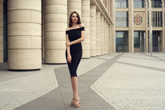 Pretty beautiful business woman in elegant black dress. Young elegant girl posing at city street. Pretty beautiful business woman in elegant black dress against Stock Photography
