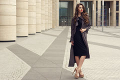 Pretty beautiful business woman in elegant black dress. Young elegant girl posing at city street. Pretty beautiful business woman in elegant black dress and gray Royalty Free Stock Photography