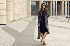Pretty beautiful business woman in elegant black dress. Young elegant girl posing at city street. Pretty beautiful business woman in elegant black dress and gray Stock Photography
