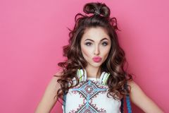 Pretty beautiful fashion cool girl with headphones wearing colorful clothes with curly hair blows a kiss with love isolated over p Stock Photos