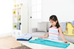 Pretty female little kid children folding clothing royalty free stock images