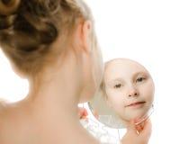Pretty beautiful girl looks in the mirror. Stock Photo
