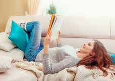 Pretty beautiful girl reading a book at sofa Royalty Free Stock Photos
