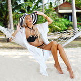 Pretty beautiful girl relaxing in hammock on a beach Stock Photos