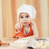 Pretty beautiful girl at the table making pies. stock photo