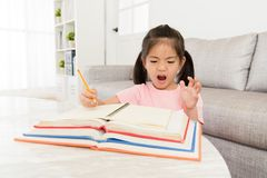 Little kid student having many school homework. Pretty beautiful little kid student having many homework must be do before back to school and writing textbook royalty free stock photo
