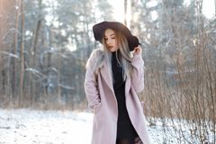 Pretty beautiful young woman in a black knitted dress in an elegant black hat in a stylish pink coat posing outdoors royalty free stock photo