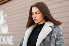 Pretty beautiful young woman model in an elegant spring gray plaid coat in a black trendy T-shirt stands