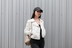 Pretty beautiful young woman with a stylish gold backpack in a fashionable white leather jacket in black jeans. In a stylish baseball cap is standing outdoors royalty free stock photography