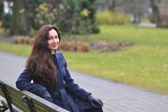 Pretty Young Woman Walking in Autumn Park Relax Coat. Pretty Beautiful Young Woman Walking in Autumn Park Relax Coat City Long Hair Make Up Stock Images