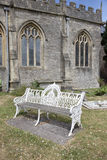 Pretty bench seat. Pretty white metal  bench seat in a church grounds Stock Photos