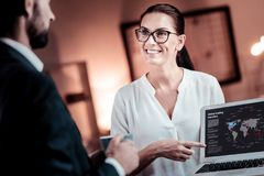 Pretty bespectacled employee holding and demonstrating the laptop. Check it out. Pretty bespectacled responsible employee holding and demonstrating the project Stock Photos