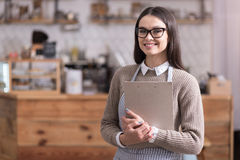 Pretty bespectacled woman smiling and holding folder. Great planes. Delighted beautiful woman smiling and holding folder while standing in a cafe Stock Images