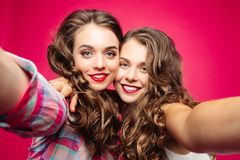 Pretty best friends taking selfie with camera. Royalty Free Stock Photo