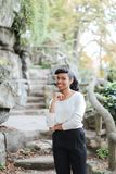 Pretty black female person standing near rock and stone stairs in park, having ponytail. stock photos