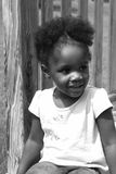 Pretty Black Girl. A black and white picture of a girl sitting on a wooden bridge Royalty Free Stock Photo