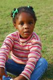 Pretty Black Girl. A beautiful young black girl is sitting in an open field on a nice fall day Stock Photography