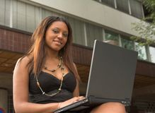 Pretty black girl with laptop. Pretty black girl sitting with the laptop outside of an office building stock photo