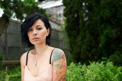 Pretty black haired girl with tattoo in the garden Royalty Free Stock Photography