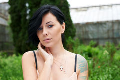 Pretty black haired girl with tattoo in the garden Stock Photos