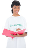 Pretty black haired volunteer writing on a notebook Royalty Free Stock Photography