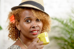A pretty black woman drinking a cup of coffee Royalty Free Stock Photography