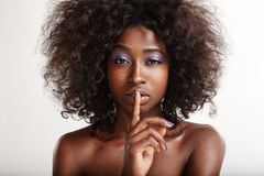 Pretty black woman with a finger on her lips making shhh!. On white Stock Image