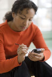 Pretty black woman on PDA. Serious beautiful African American woman using stylus and PDA Stock Image