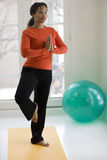 Pretty black woman practicing yoga. Young African American woman in yoga Tree pose at home Stock Photo
