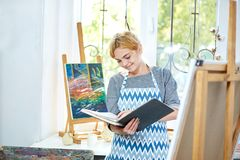 Pretty blode girl looking on a album and smiling. Art concept, royalty free stock photo